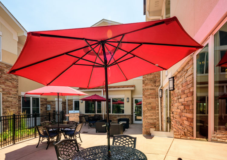 Patio with umbrellas - AltaVita Assisted Living in Longmont
